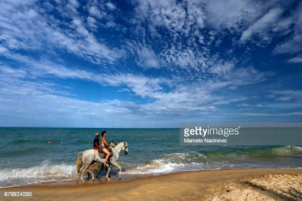 Two people riding horses on the beach in Trancoso