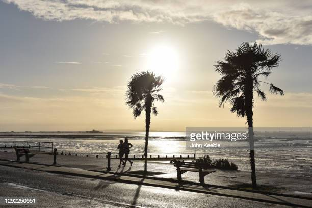 Two people run along the promenade as Essex goes into tier 4 on December 20, 2020 in Southend on Sea, England. As from today all non essential shops...