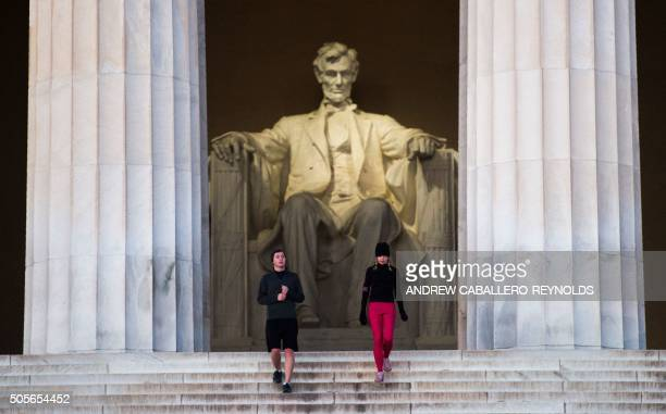 Two people run down the stairs near the Lincoln Memorial early in Washington DC on January 19 2016 / AFP / AFP PHOTO / andrew caballeroreynolds