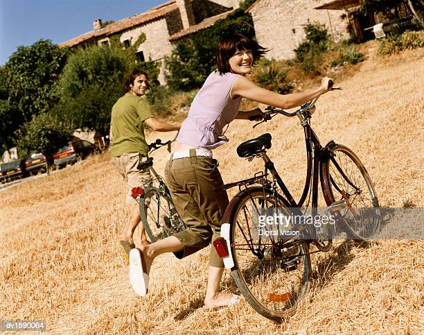 Two People Running in a Field Holding Their Bicycles