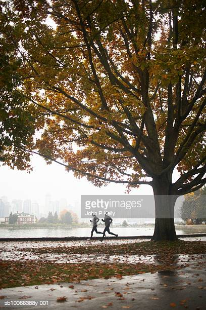 two people running in park - stanley park vancouver canada stock photos and pictures
