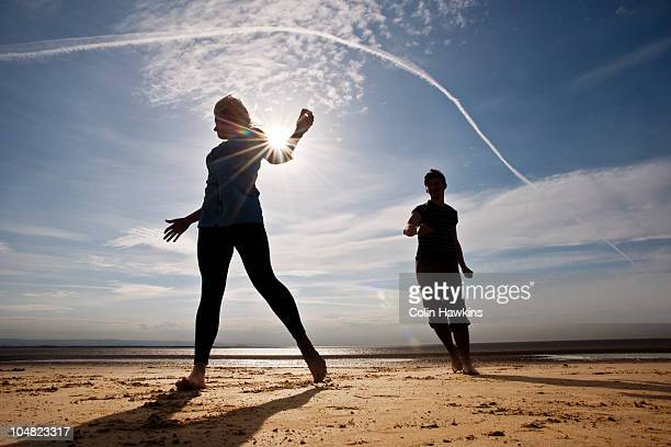 two people running on beach - colin hawkins stock pictures, royalty-free photos & images