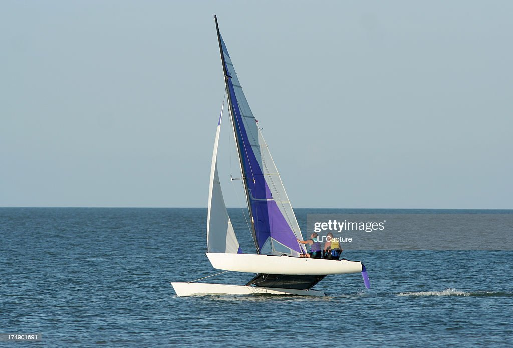 Two people sailing a catamaran in open water : Stock Photo