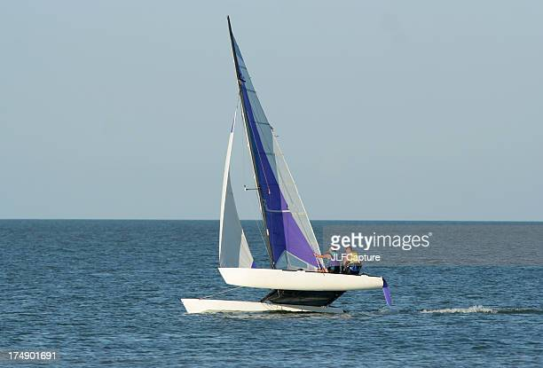 two people sailing a catamaran in open water - catamaran stock photos and pictures