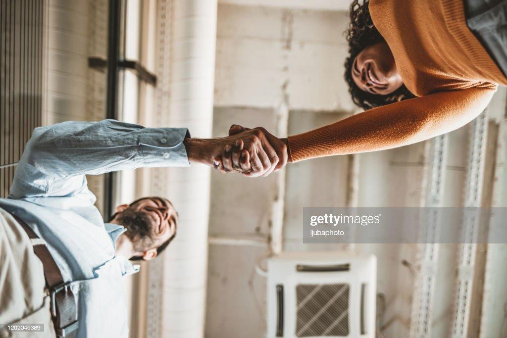 Duas pessoas apertando as mãos : Foto de stock