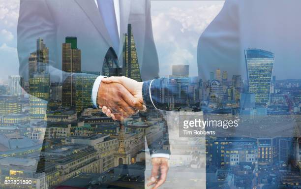 two people shaking hands with london skyline - negócios internacionais - fotografias e filmes do acervo