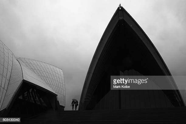 Two people share an umbrella to shelter from the rain as they visit the Sydney Opera House on January 5 2016 in Sydney Australia Sydney has...