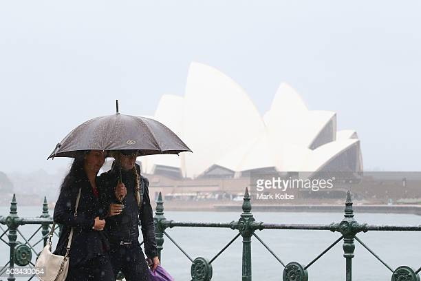 Two people share an umbrella to shelter from the rain as they walk through Circular Quay on January 5 2016 in Sydney Australia Sydney has experienced...