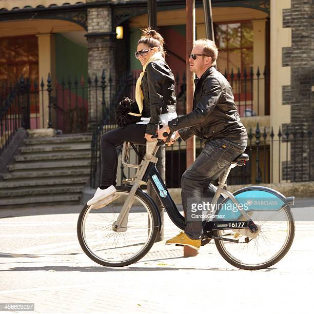 two people sharing a london boris bike - barclays cycle hire stock pictures, royalty-free photos & images