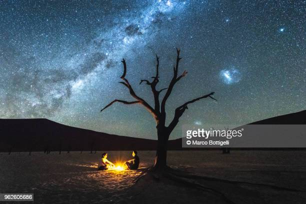 Two people sheltering at night under a dead acacia tree in Deadvlei