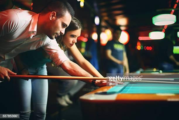 Zwei Personen shooting pool bei Nacht am Wochenende.