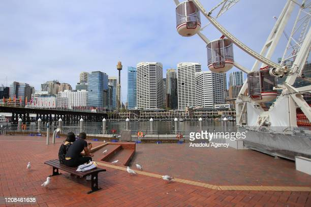 Two people sit on a bench in an empty Darling Harbour in Sydney, Australia, on March 28, 2020. Australian governments are now turning to...