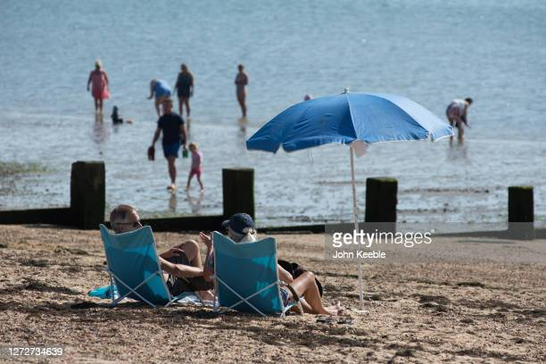 Two people sit on deck chairs on the beach as people walk out into the sea on September 14 2020 in Southend on Sea England Parts of the UK are...