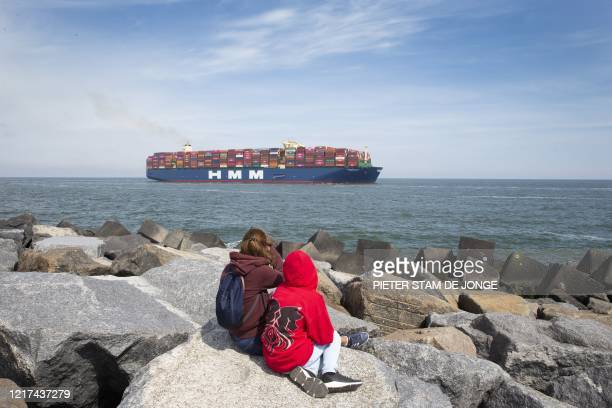 Two people sit on rocks as the world largest container vessel HMM Algeciras approach the port of Rotterdam on June 3, 2020. / Netherlands OUT