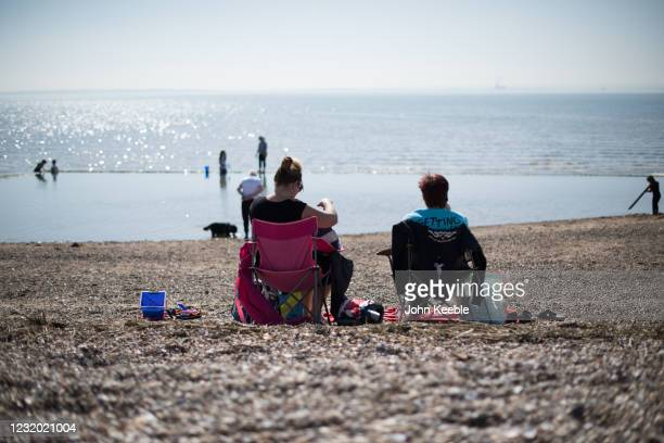 Two people sit on the beach on March 30, 2021 in Southend, United Kingdom. Despite todays temperature heading towards 24 degrees, next week is set to...