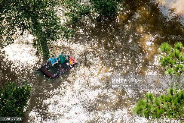 Two people sit on the roof of a vehicle trapped in floodwaters from Hurricane Florence on September 17 2018 in Wallace South Carolina Many rivers in...