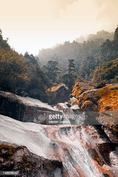 two people sitting along the seven dragon ladies pond waterfalls on cangshan mountain. - merten snijders stock pictures, royalty-free photos & images