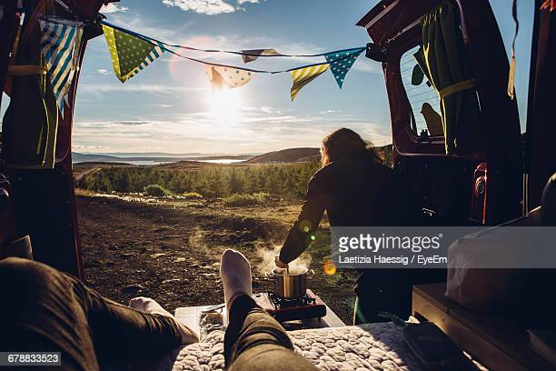 Two People Sitting In Campervan Cooking And Looking At View