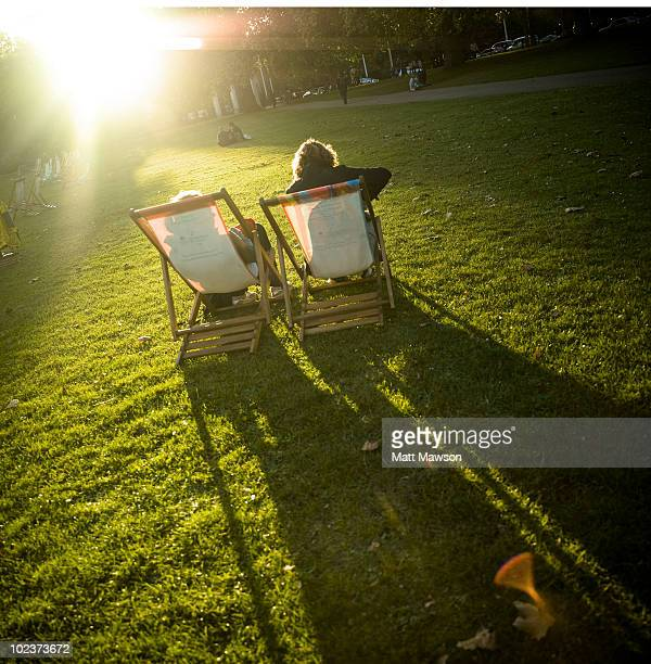 Two people sitting in deckchairs in a park