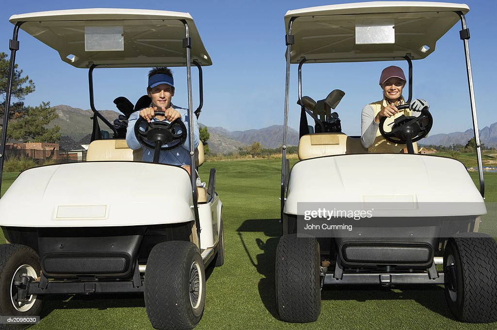 Two People Sitting in Golf Buggies : Stock Photo
