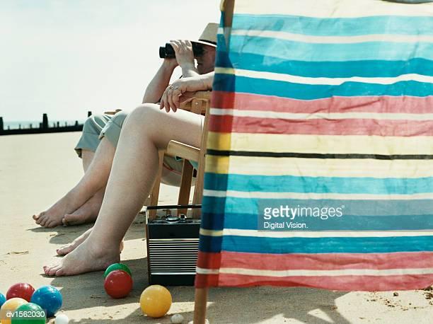 Two People Sitting on Beach Behind a Windbreaker, Man Looking at View Trough Binoculars