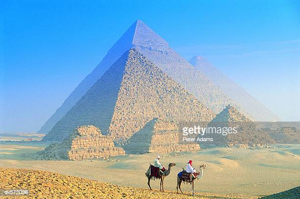 two people sitting on camels in front of the great pyramids, giza, egypt - giza pyramids stock pictures, royalty-free photos & images