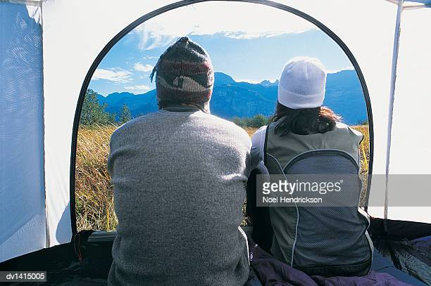 Two People Sitting Side by Side, Looking at the View out of a Tent