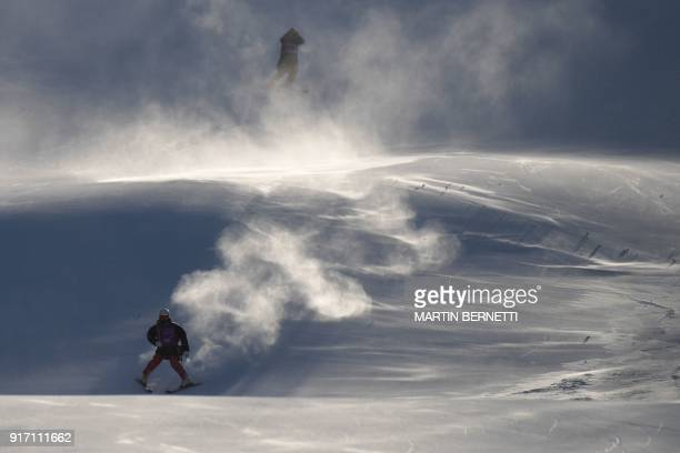 Two people ski slowly down the slopes after the Women's Giant Slalom was cancelled because of strong winds at the Jeongseon Alpine Center during the...
