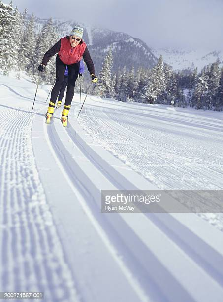 two people skiing down track in snow - nordic skiing event stock pictures, royalty-free photos & images