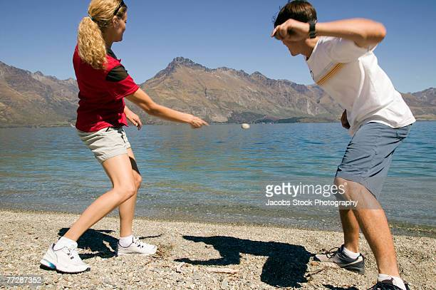 Two people skipping rocks on mountain lake