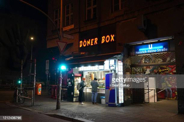 Two people stand at a Doner kebab shop on a street corner that would normally be packed with people waiting to get in to the KitKat Club around the...