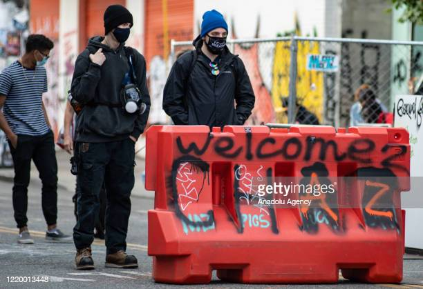 Two people stand at an entrance to the âCapitol Hill Organized Protestâ formerly known as the âCapitol Hill Autonomous Zoneâ in Seattle Washington on...