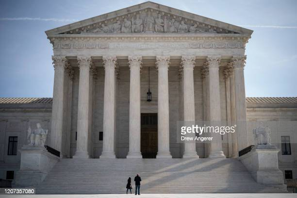 Two people stand at the base of the US Supreme Court on March 16 2020 in Washington DC The Supreme Court announced on Monday that it would postpone...