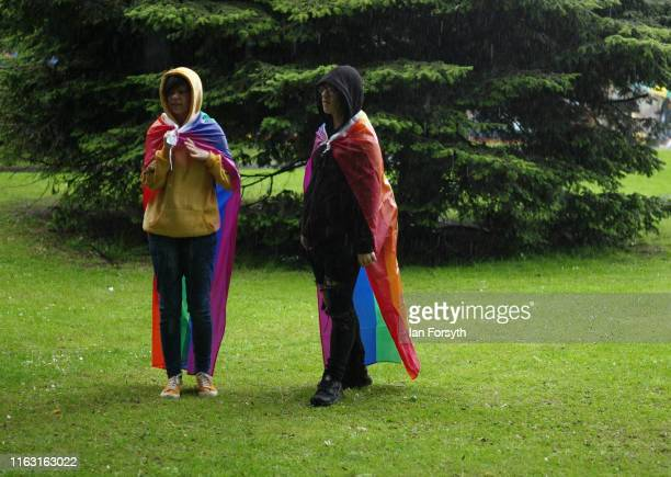 Two people stand in a heavy rain shower as they take part in the Newcastle Pride Festival parade on July 20, 2019 in Newcastle upon Tyne, England. To...