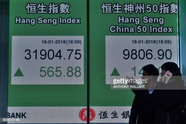 Two people stand next to a stocks display board after the Hang Seng Index leapt 181 percent or 56588 points to close at 3190475 in Hong Kong on...