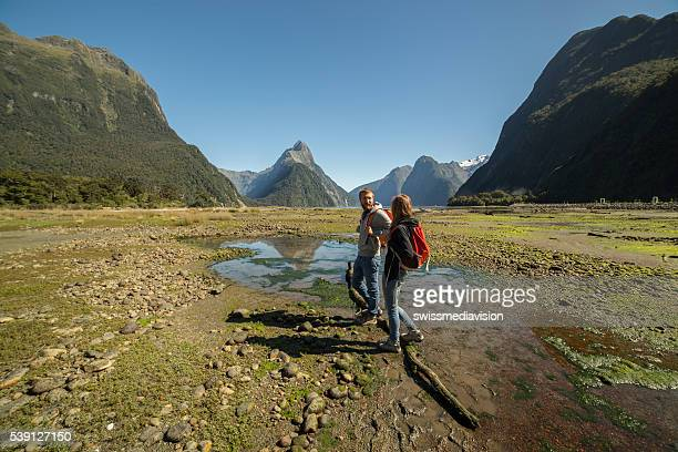 Two people stand on log at Milford sound, NZ
