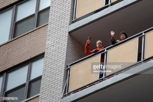 Two people stand on their balcony waving and ringing a bell for healthcare workers during the 7PM nightly cheer amid the coronavirus pandemic on...