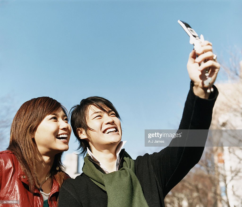 Two People Stand Outdoors, Man Photographing Themselves With a Mobile Phone : Stock Photo