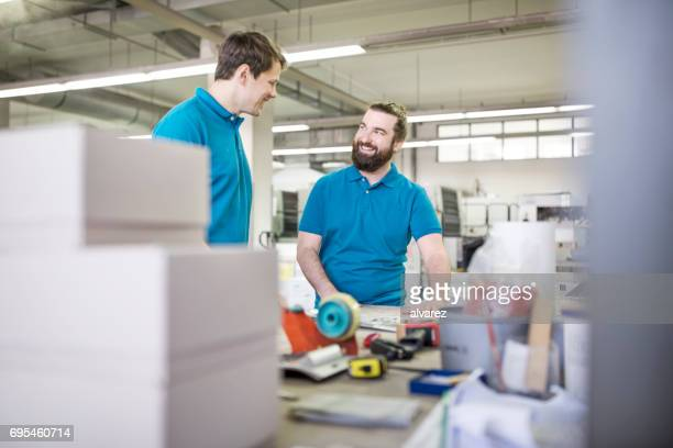 Two people standing and discussing in printing plant