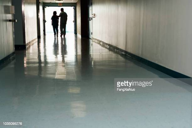 two people standing at end of corridor in hospital - grief stock pictures, royalty-free photos & images