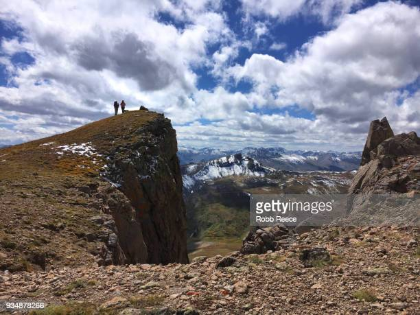 two people standing on a remote mountain top trail - robb reece stockfoto's en -beelden