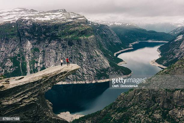 two people standing  on the trolltunga - cañón tipo de valle fotografías e imágenes de stock