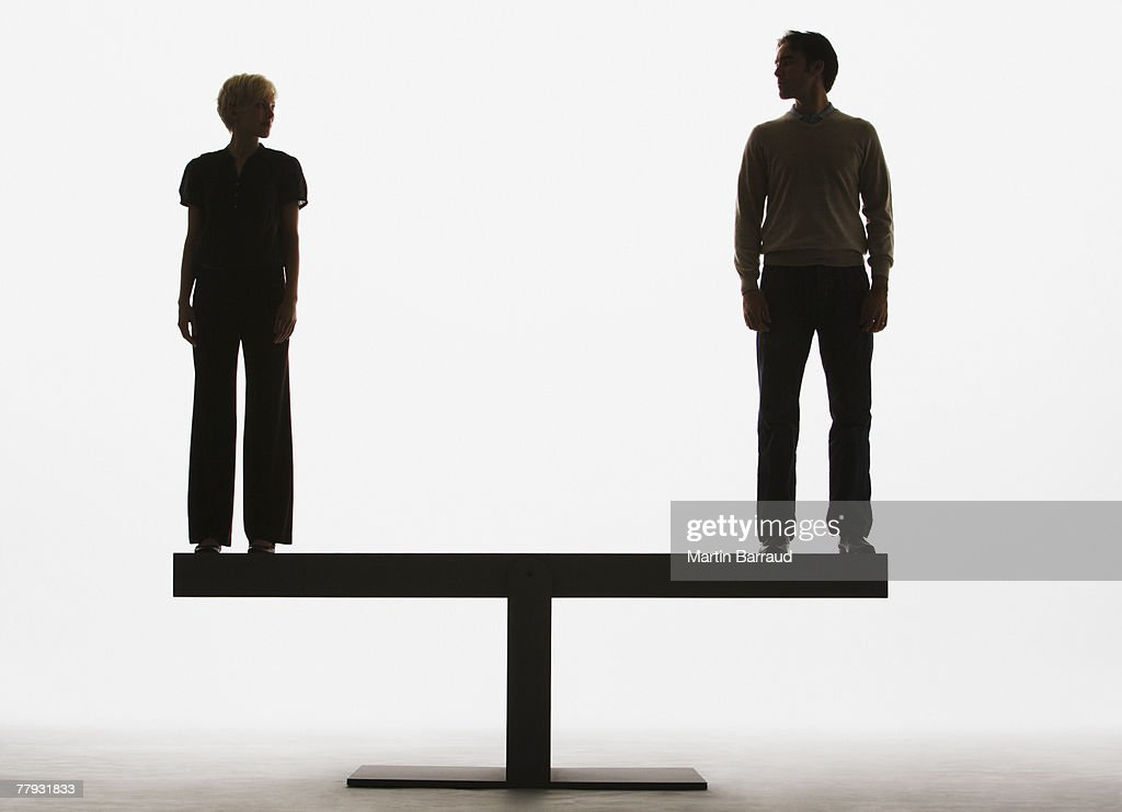 Two people standing on top of a plank : Stock Photo