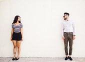 Two people standing on white wall background