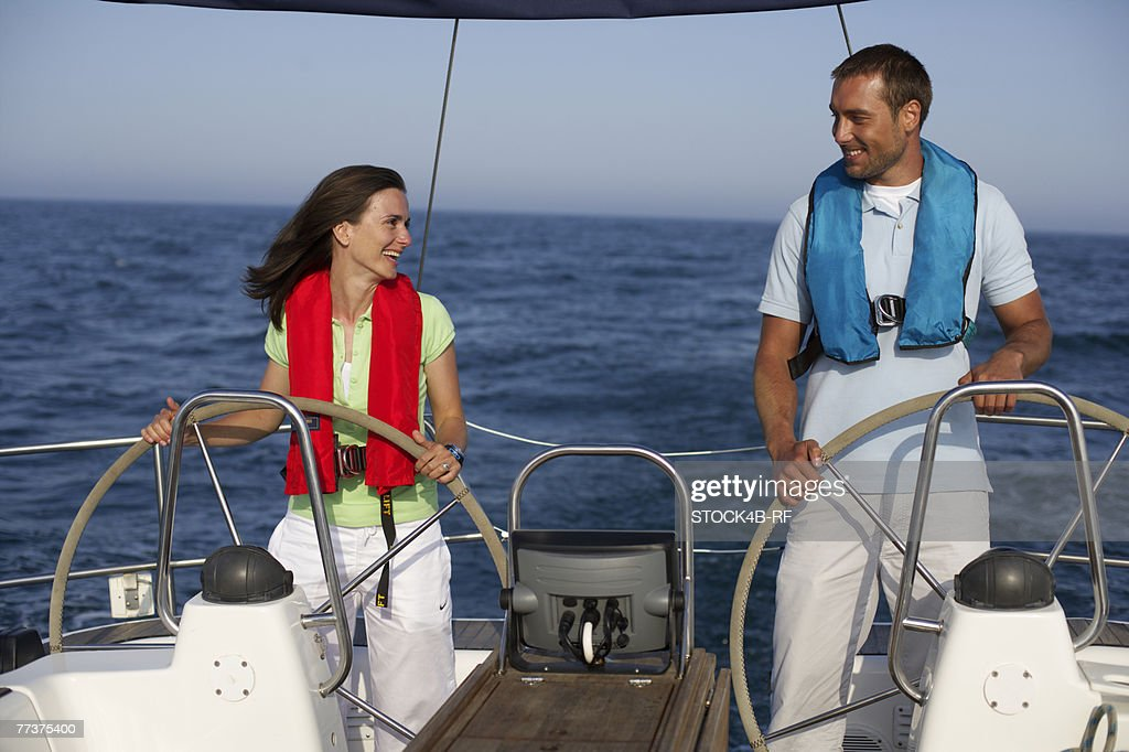 Two people steering a boat : Photo