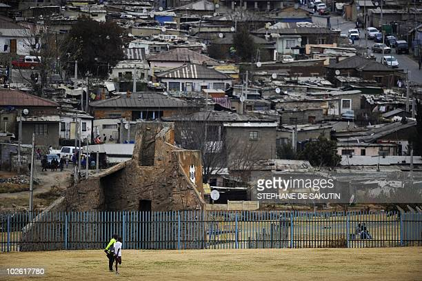Two people stretch in a field next to Alexandra Township near Johannesburg where the Football For Hope tournament opened on July 4 2010 According to...