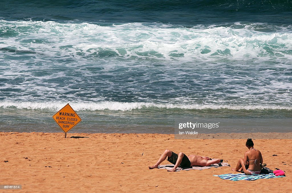 Two People Sunbath On The The Closed Avalon Beach After A Shark On A Surfer