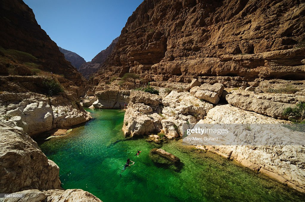 Two people swimming in the turqoise waters of Wadi Shab, Oman : Stock Photo