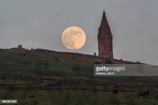 Two people take a selfie with a selfie stick beside Hartshead Pike as the Flower Moon rises at 986% on May 28 2018 in Manchester England The tower...