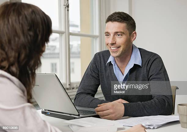 Two people talking at desk